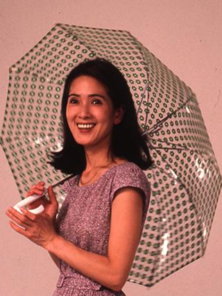 紫のワンピースを着て傘をさしているいしだあゆみの画像