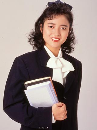 パーマヘアをハーフアップにし、本を持つアイドル時代の三田寛子